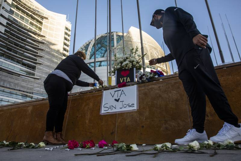 Mourners lay flowers at a vigil for shooting victims