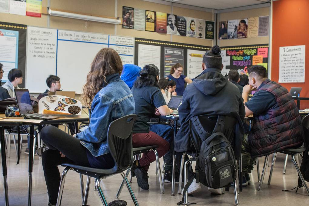 High school students sit on chairs behind tables facing a teacher, who stands.