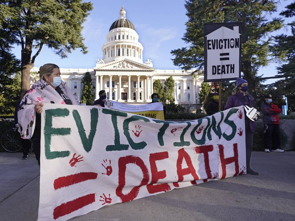 """Demonstrators hold signs that read """"Evictions = Death"""" in front of the Capitol in Sacramento."""