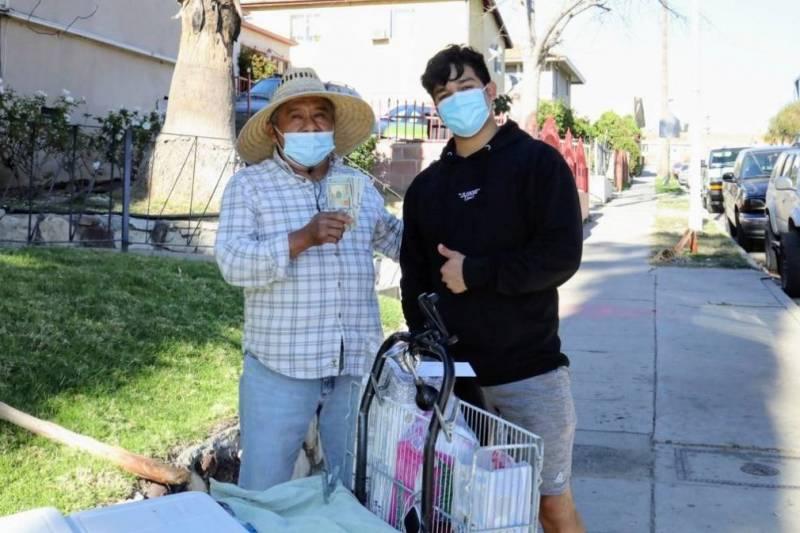 Una imagen de Jesús Morales, influencer de TikTok, y un vendedor ambulante. El vendedor lleva puesto un sombrero para protegerse del sol y en sus manos unos billetes que Morales le dio.