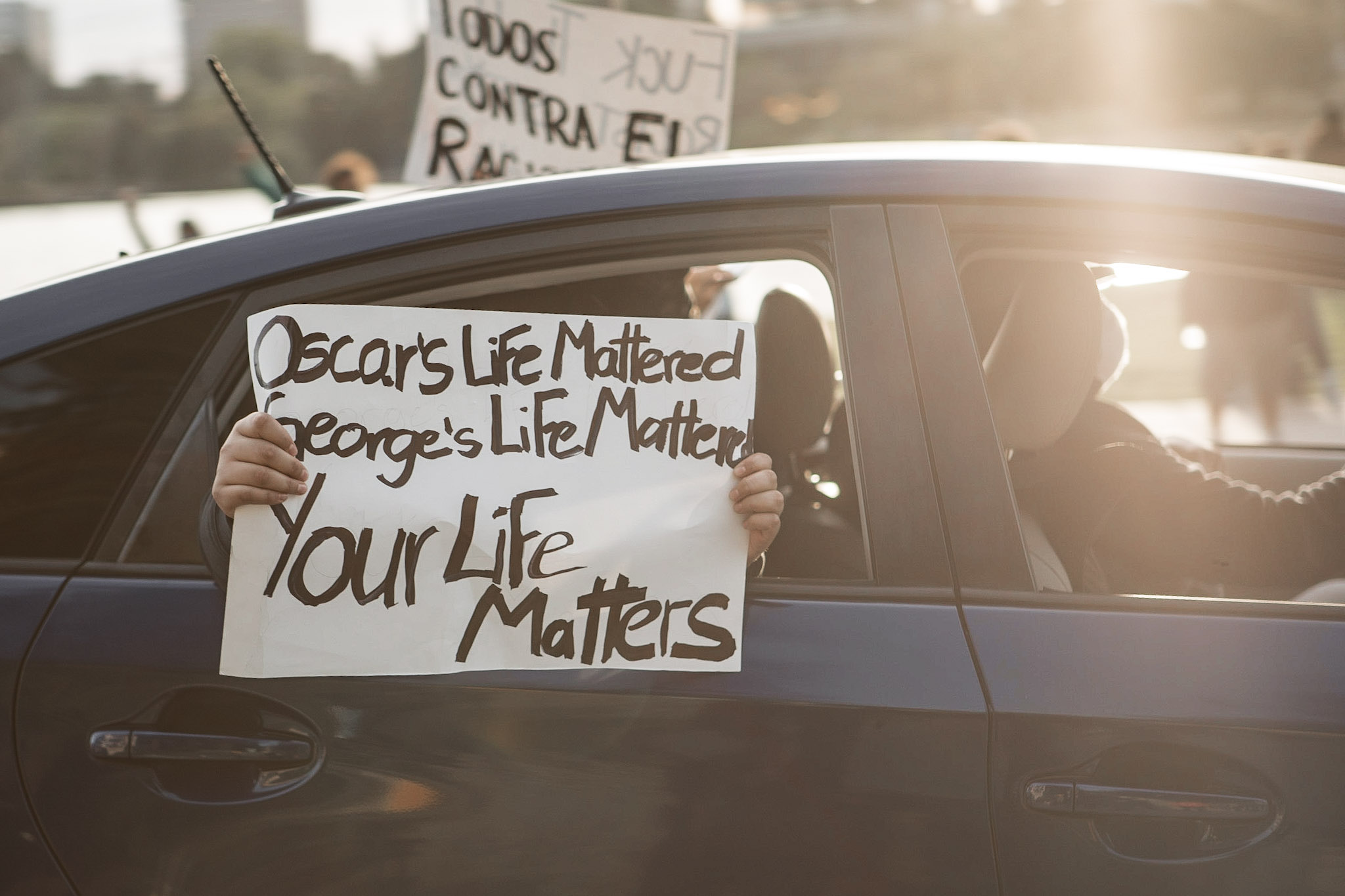 A protester inside a car holds up a sign calling for racial justice. It reads Oscar's Life Mattered, George's Life Matters, Your Life Matters.