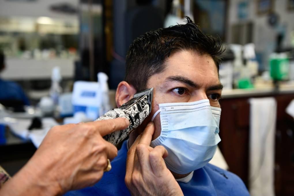 Carlos Hernández sostiene su cubrebocas mientras Sarah Cordiey le corta el pelo en Spiros Barber Shop en Long Beach, el 9 de junio de 2021.