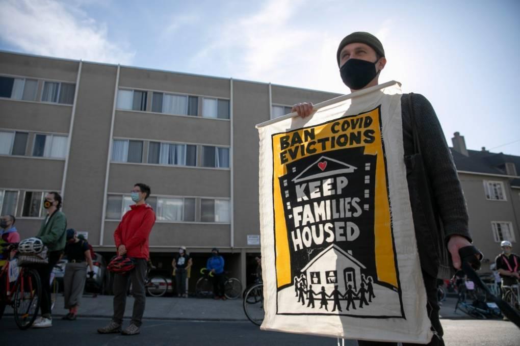 Un hombre sostiene una pancarta en una calle. Hay otras personas a su alrededor.