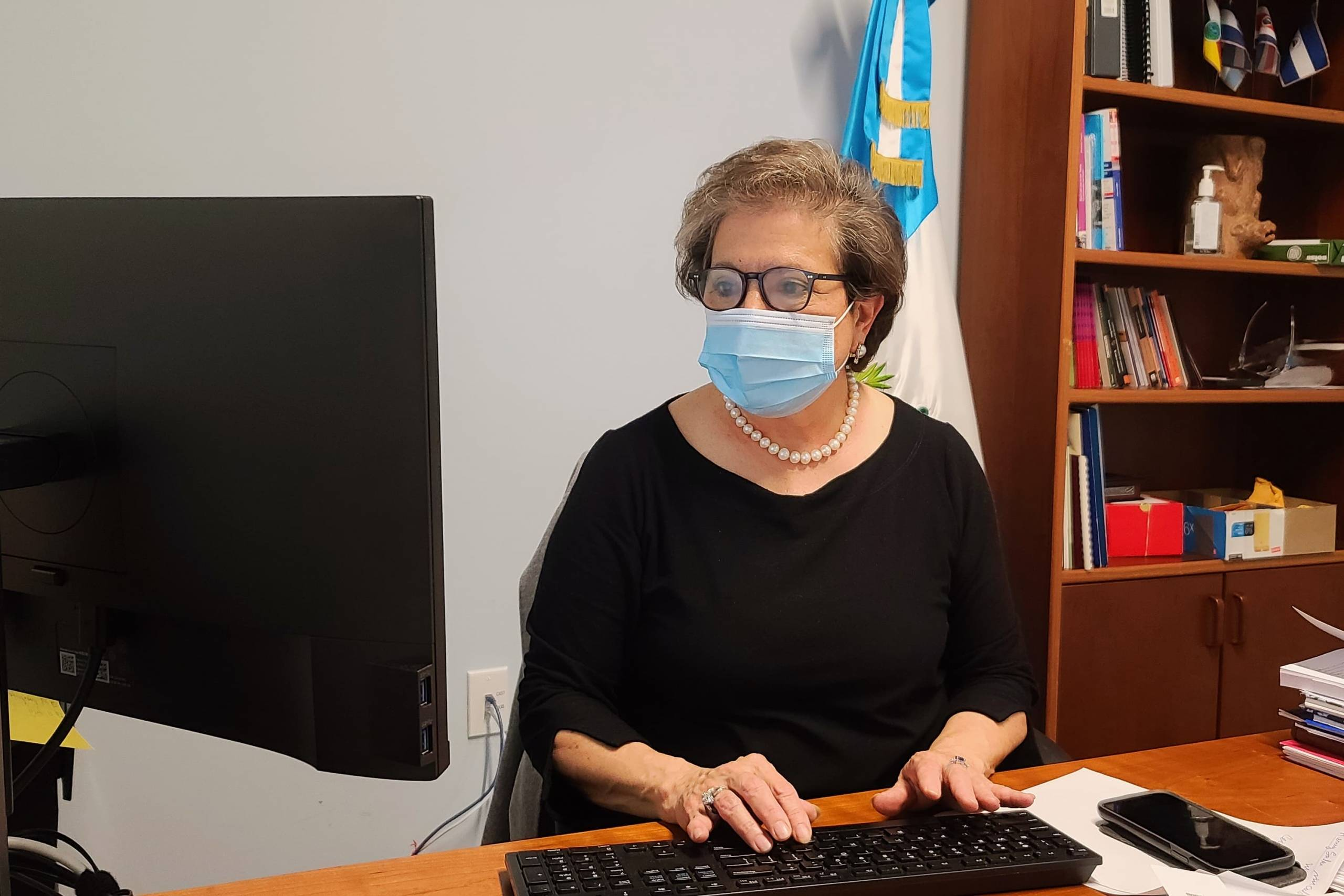 Sylvia Wohlers Gomar de Meie, the Guatemalan consul general in San Francisco, types on her computer in her office. She is wearing glasses and a blue facemask.