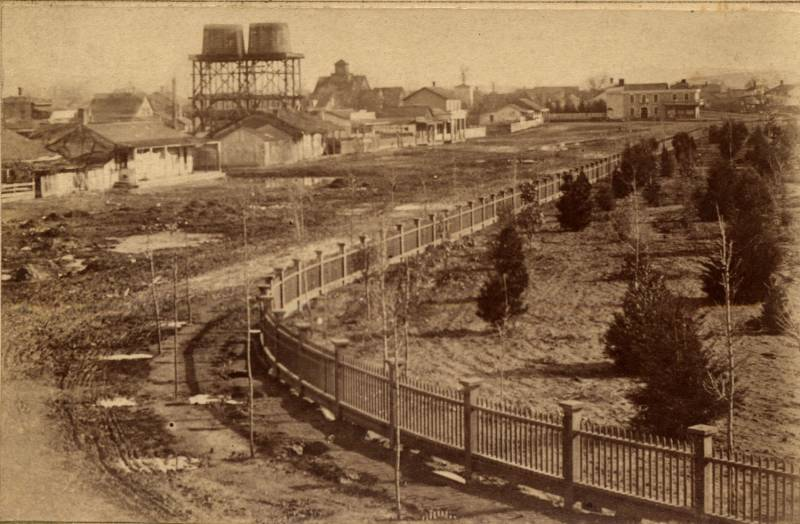 The First Market Street Chinatown in San Jose was built in 1866. In this photo, the towers of McKenzie Iron Foundry, the San Jose Brewery and San Jose waterworks is visible in the background.