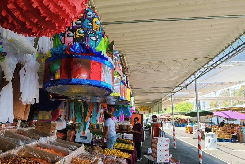 A piñata stand, with piñatas all around, next to a fruit and vegetable stand, some workers are visible moving boxes in the background.
