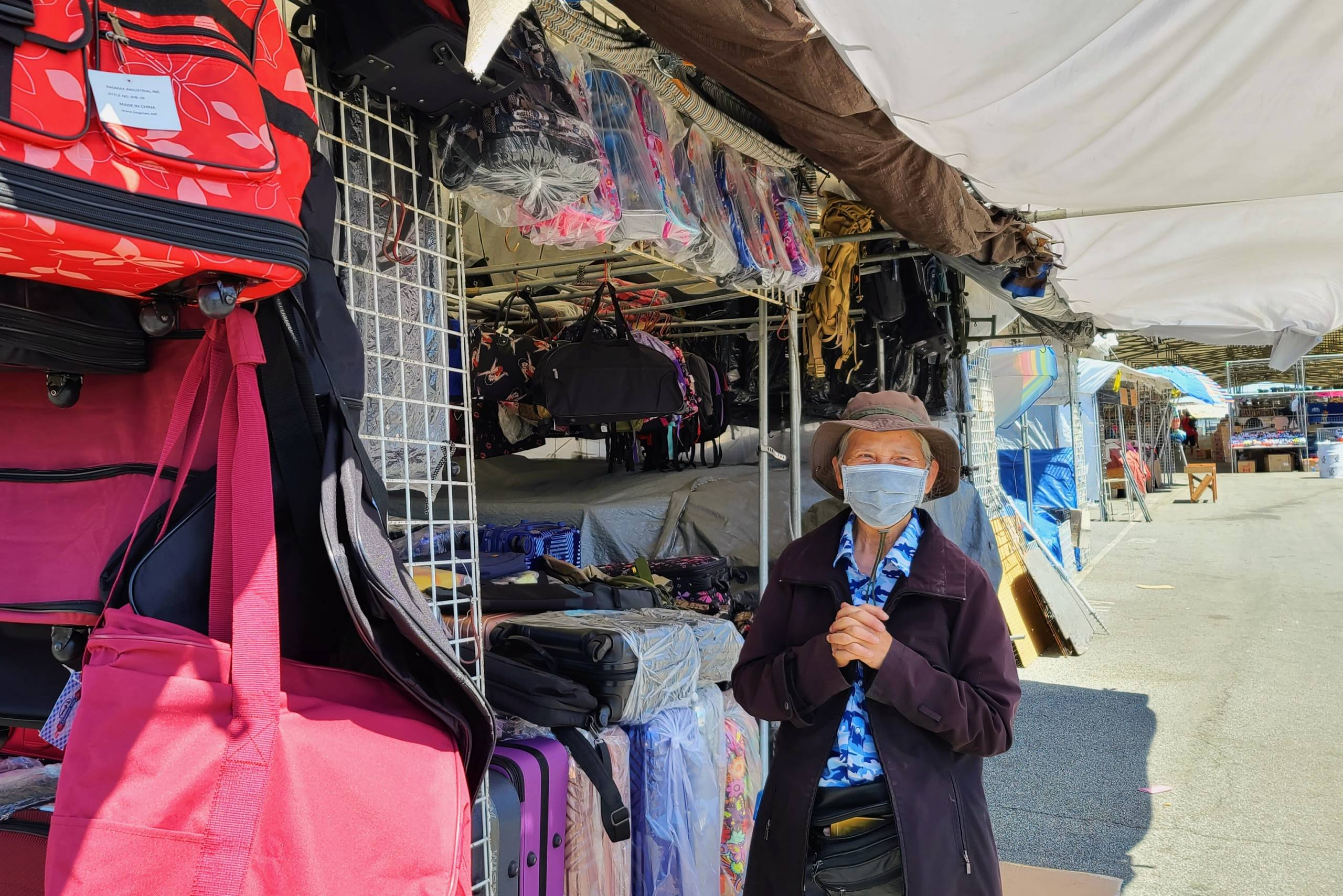 Chau Nguyen stands next to her stall covered in the luggage bags and backpacks she sells.