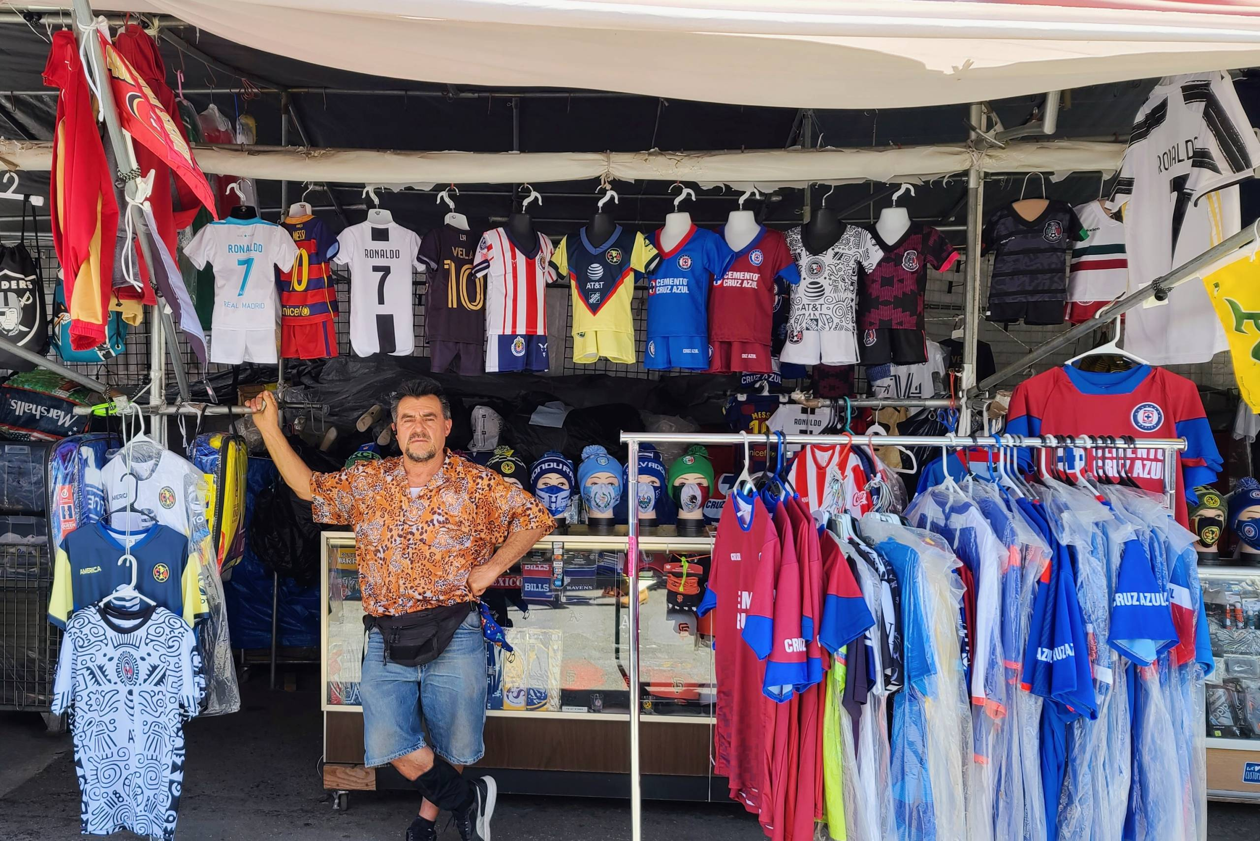 Mario Davila stands in front of his stall that is covered in jerseys of different soccer teams in all different sizes. They hang next to him, on top of him, all around him.