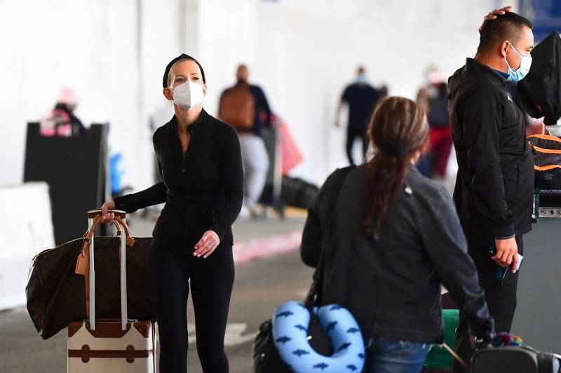 A person wearing a facemask walks through an airport.