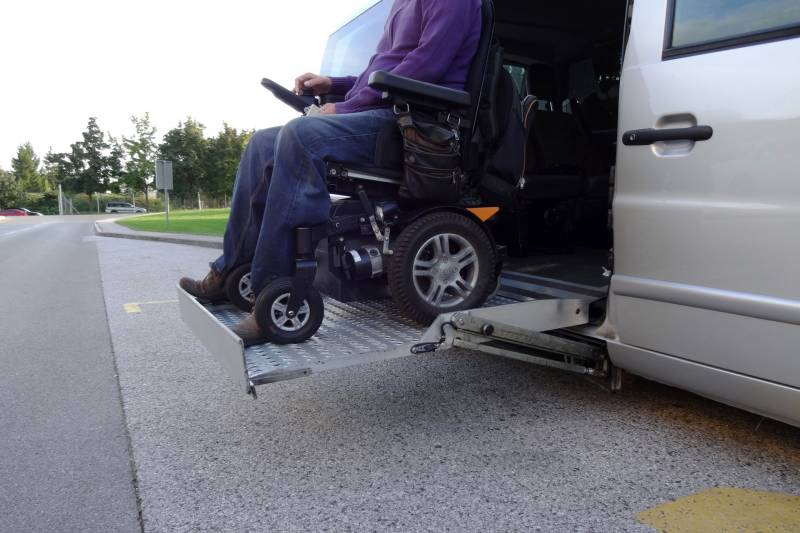 Man on motorized wheelchair on a lift on a wheelchair accessible vehicle
