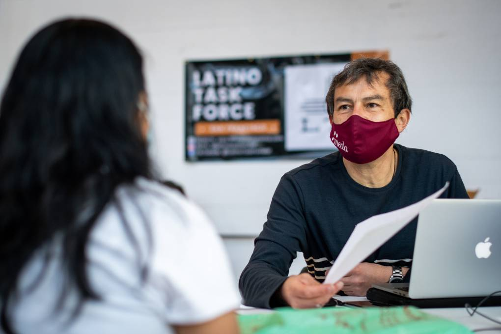 Dairo Romero, community initiatives manager at MEDA, sits at a table as he helps out a person file their taxes.