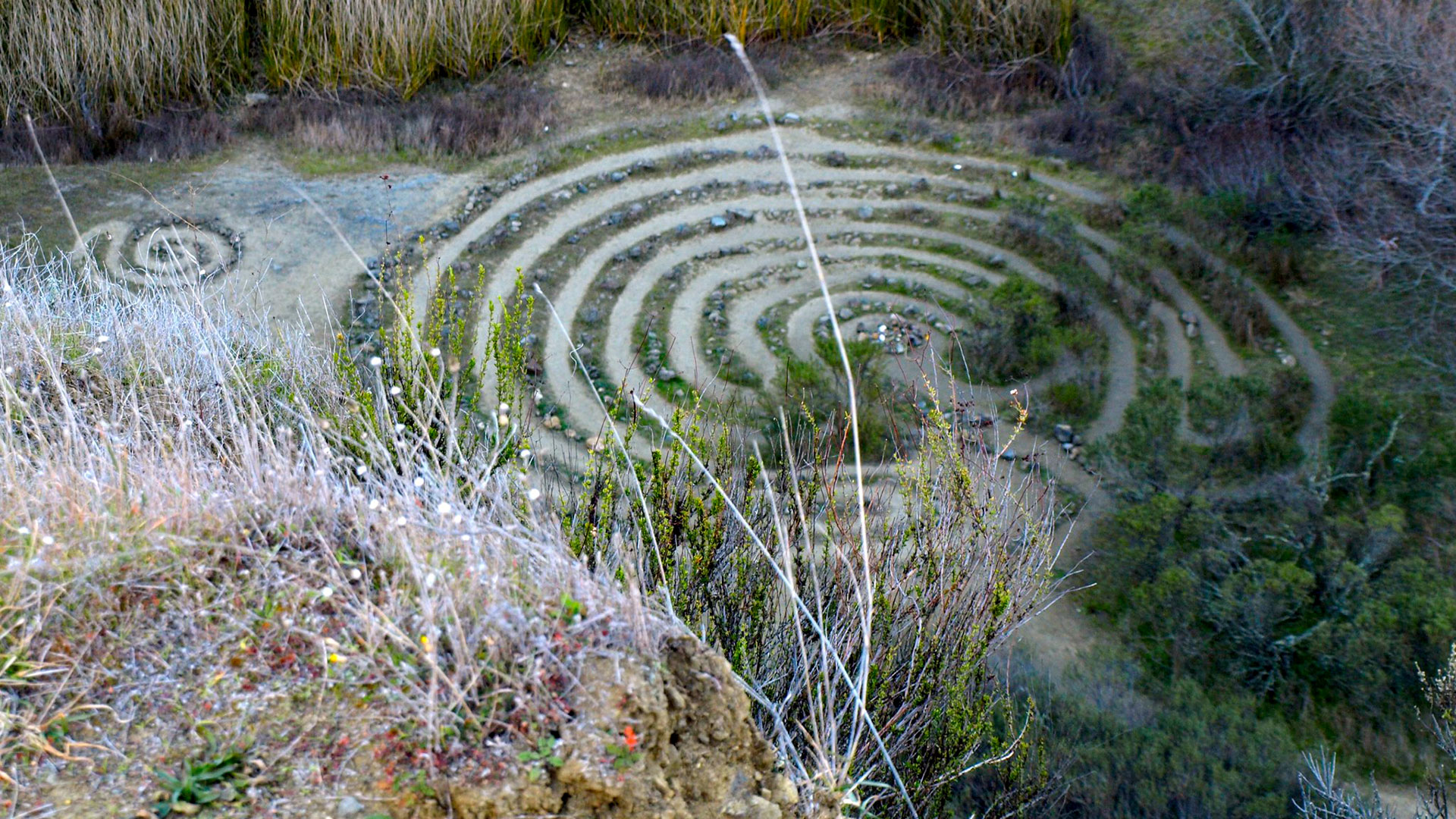 A labyrinth made of grass and stones sits at the bottom of a quarry in Sibley Volcanic Regional Preserve.