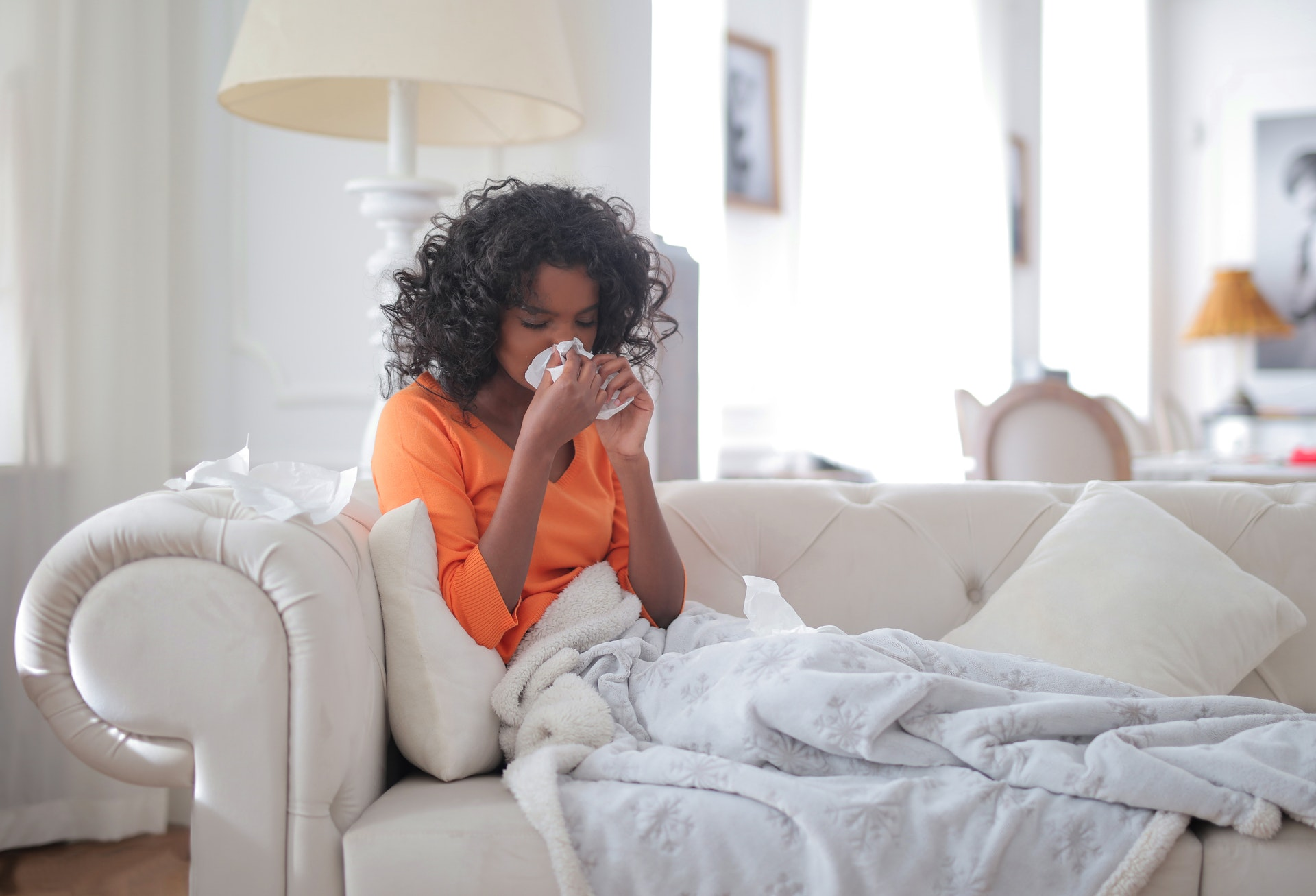 Woman on a couch wrapped in a blanket, sneezing