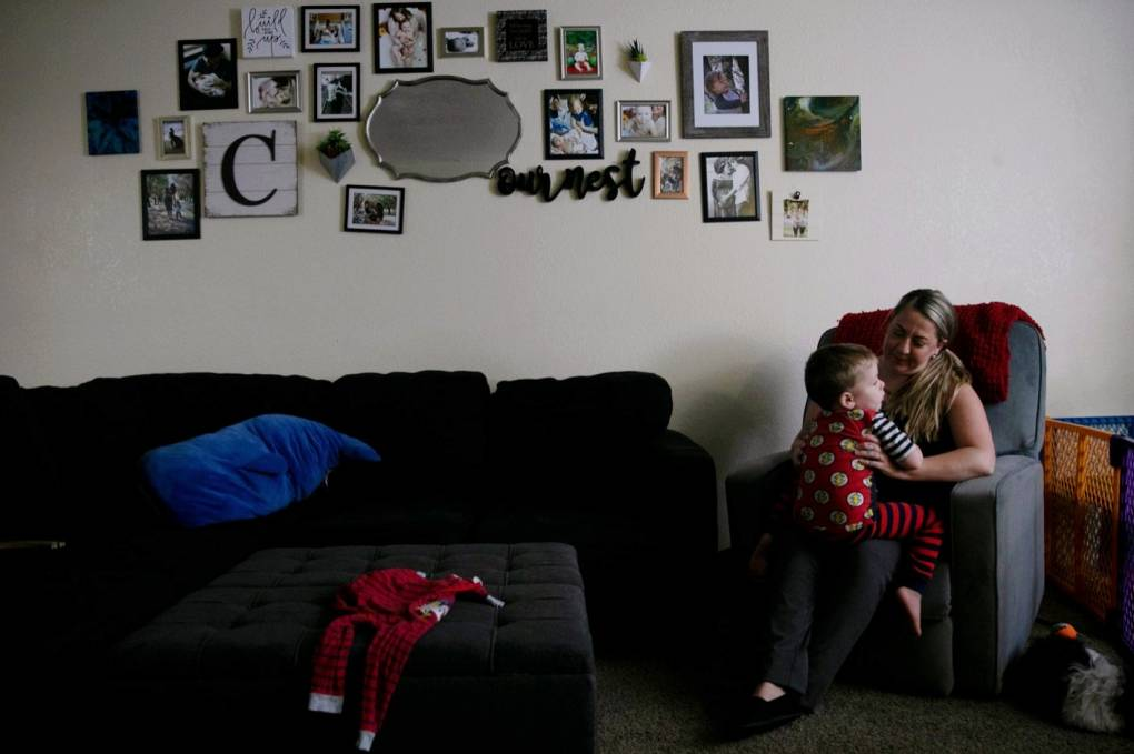 An adult with blond hair sits on a couch and carries an infant. Both are in a dark living room. There are many photos hung on the wall besides them.