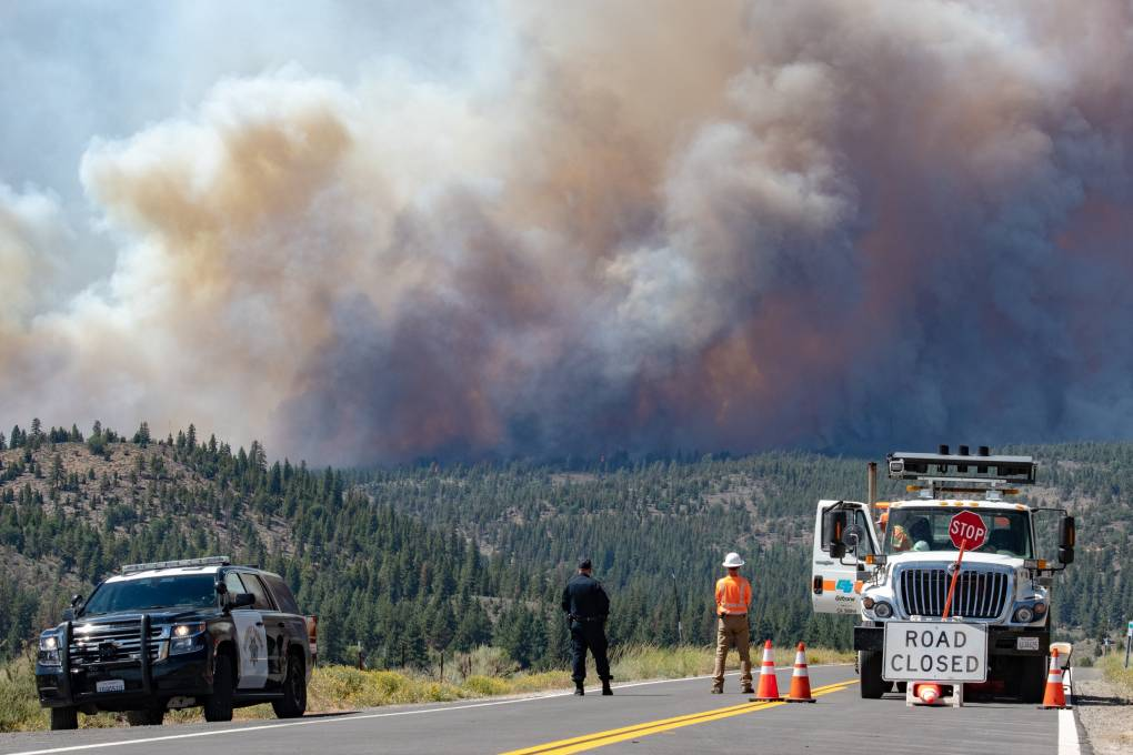 Two people stand in the middle of the road as they watch the horizon where massive plumes of smoke have grown caused by the Beckwourth Fire Complex.