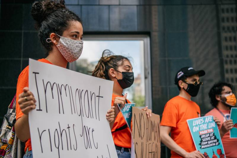 A group of youth wearing orange shirts and facemasks hold up several signs that read 'Immigrant rights are human rights.'