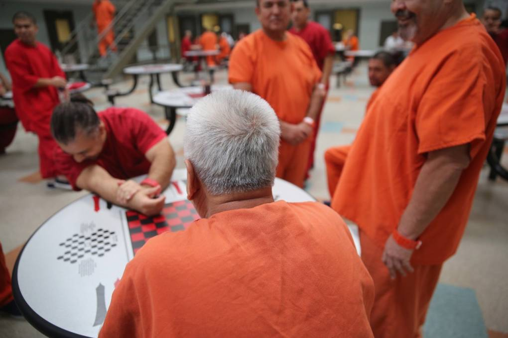 Detainees in orange jumpsuits gather around a table.