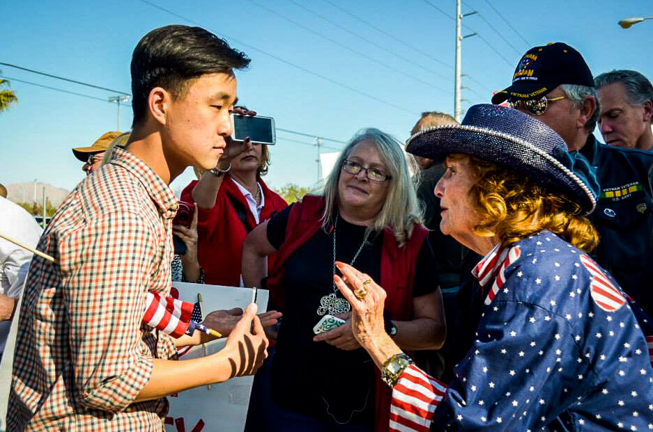 Ju Hong talking with a participant at an immigration rally.