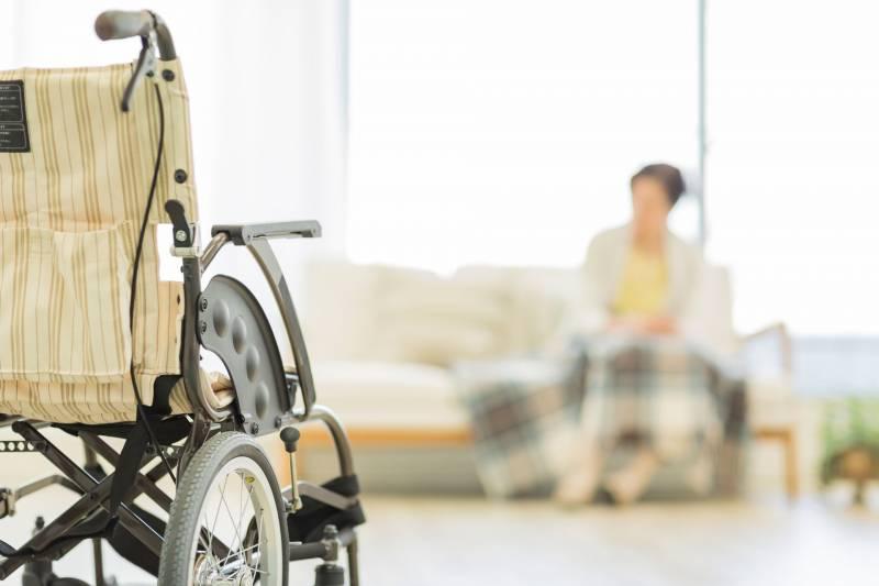 empty wheelchair in foreground, blurry nursing home resident in background