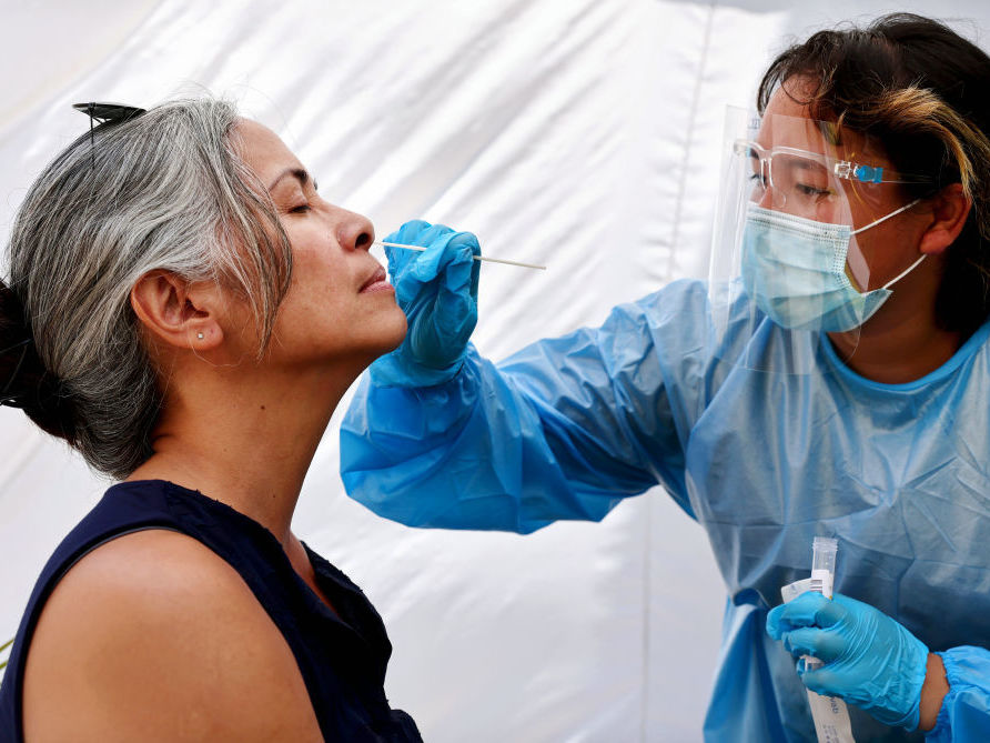 A medical assistant stands over a woman and takes a swab from her nose.
