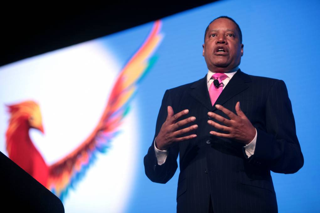 Larry Elder in a dark suit and pink tie, with a projected image of a phoenix on the wall behind him