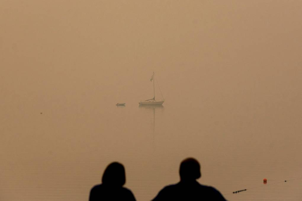 A couple watches from the shore a distant boat on the lake, which has been completely blanketed by smoke.