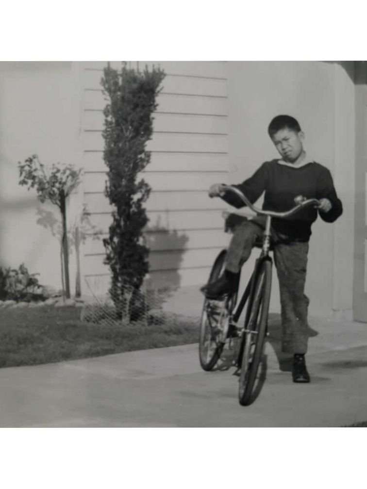 A young Filipino boy straddles a bike in front of a house in 1960.