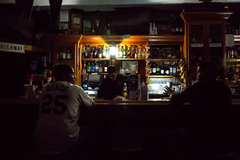 The front side of a bar. The establishment is dark as its lights are not on and only a few lamps provide light to a bartender that is attending to two customers who are talking to one another.
