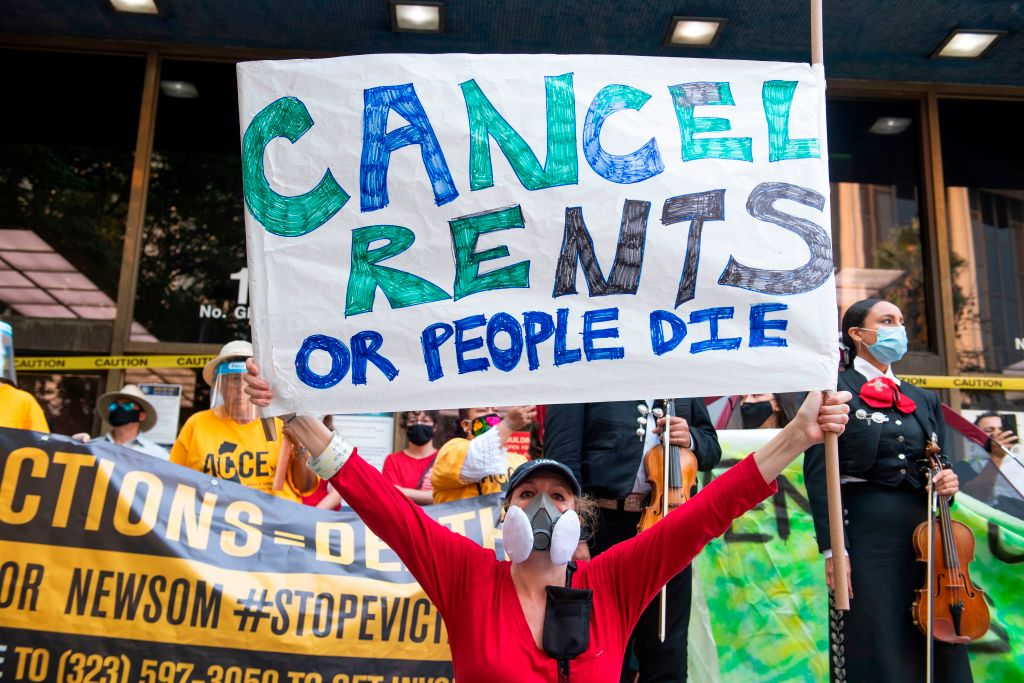 """A woman holds up a big sign that says """"Cancel Rents of People Die."""""""