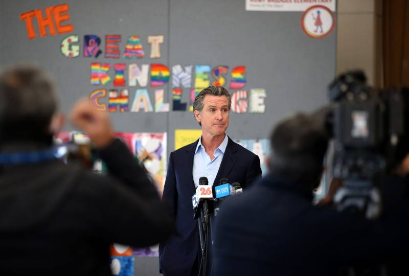 """Gavin Newsom, without a tie, speaks into a bank of microphones in front of a board with colorful letters that spell """"The Great Kindness Challenge."""""""
