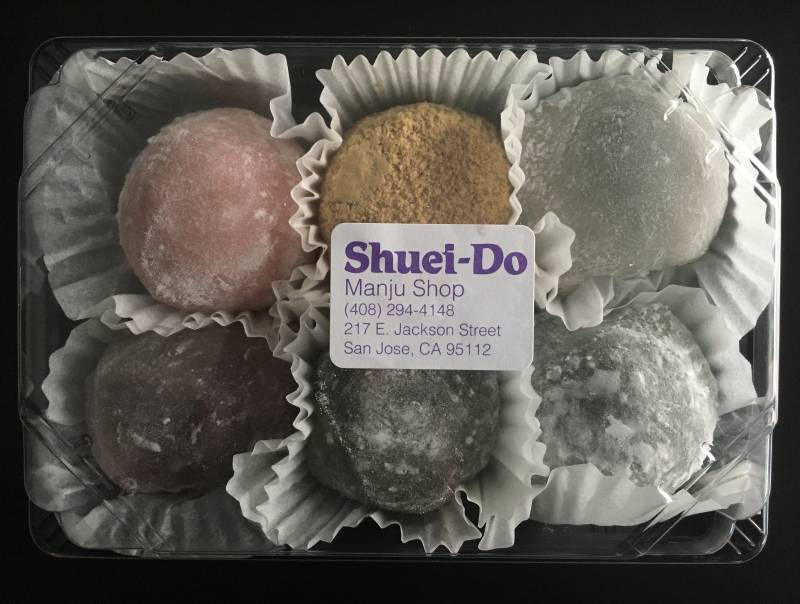 A box of six colorful mochi, with a plastic top and the shop's label on it.