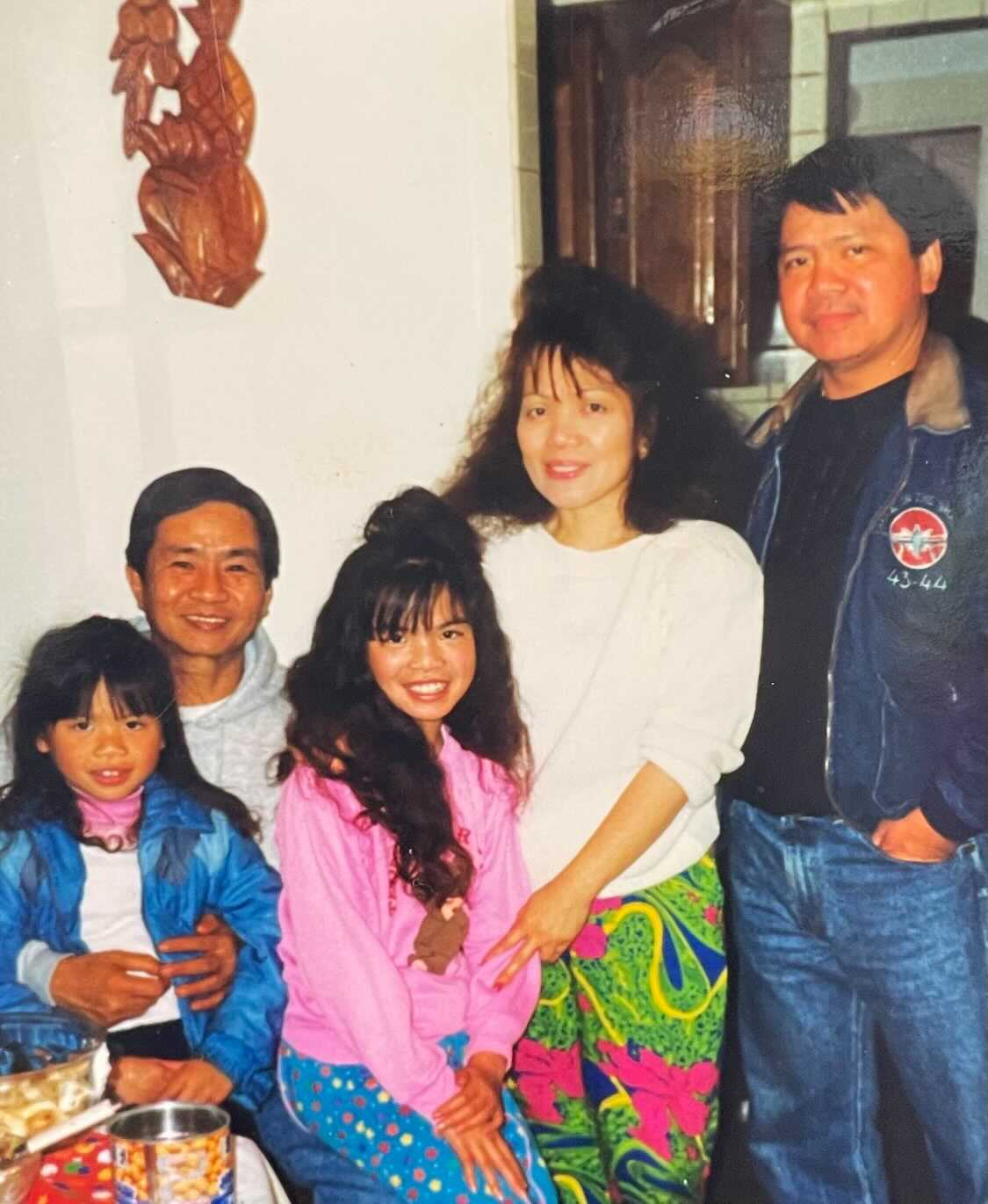A Filipino American family poses for a photograph. They are wearing clothes and have hairstyles that were popular in the 1990s.