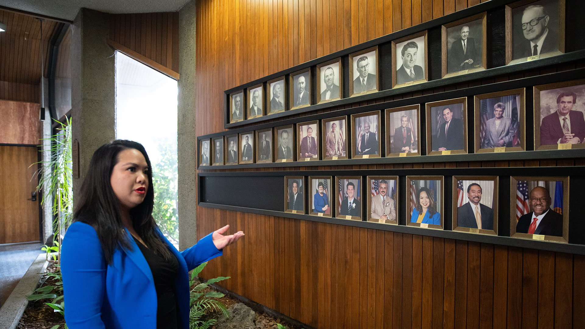 Daly City Mayor Juslyn Manalo points to a wall of past mayors on the wall of City Hall. For many years white men dominated, but more recently the city's diverse community is represented here too.