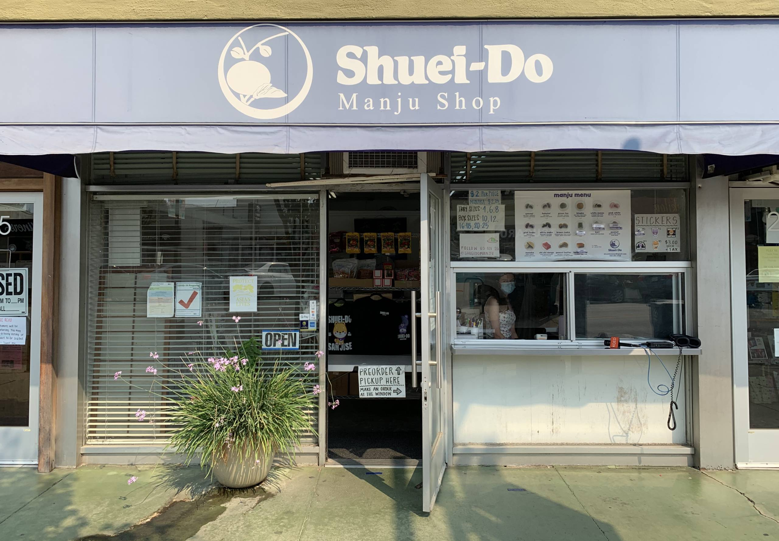 The outside of Shuei-Do, a mochi shop, with its door wide open. It has blue awning and beige lettering.
