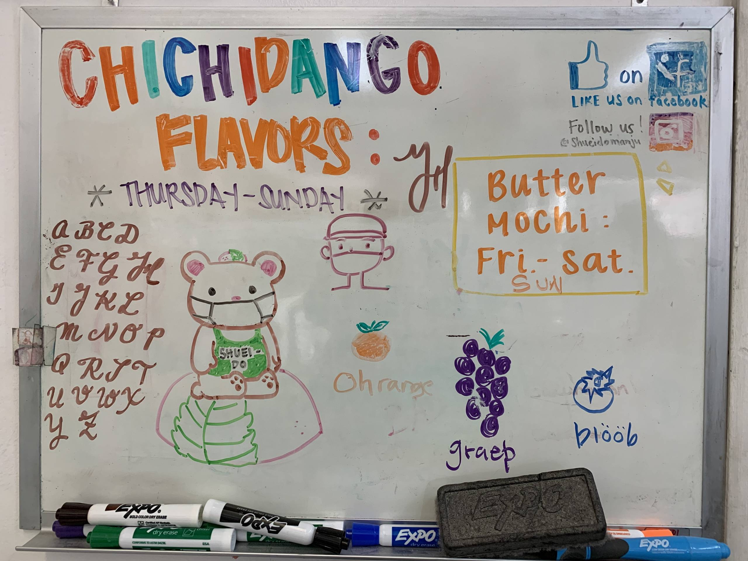 """A whiteboard details the treats at Shuei-Do, saying """"chichidango flavors"""" in multicolored marker, with a drawing of a bear with a mask on top of a mochi pastry."""