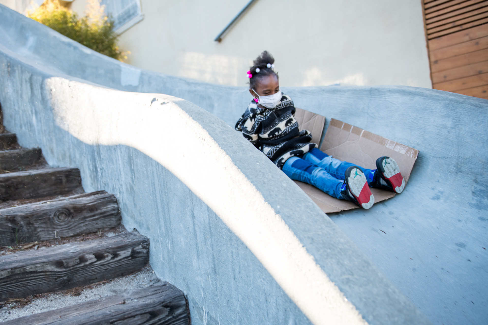 young child on slide wearing a mask