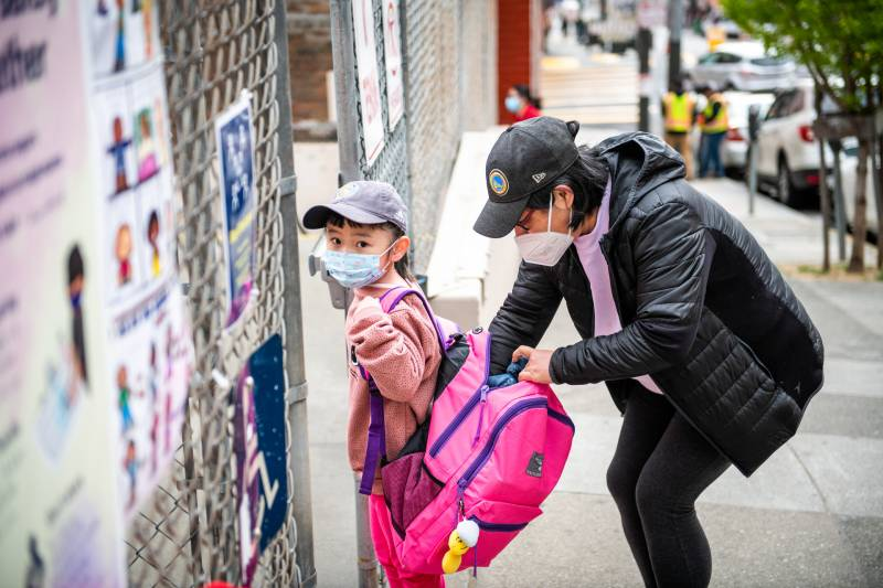 Mom crouches down with hand in young kid's enormous pink backpack, both wearing baseball caps and masks