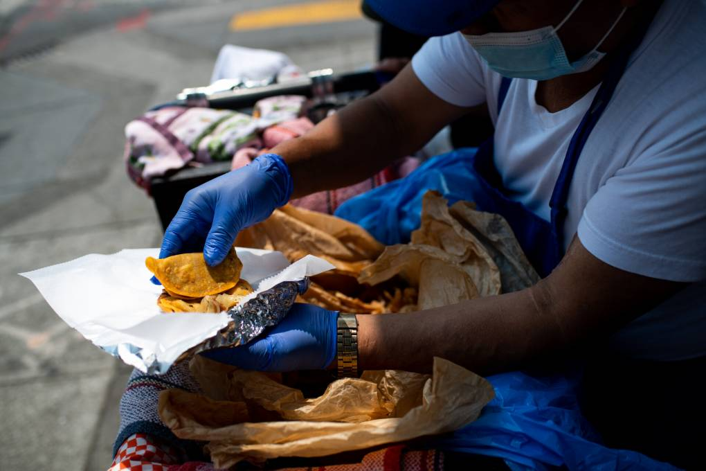 A food vendor stands behind his basket where he keeps his tacos wrapped, wearing gloves and standing in the shade on a sunny day.