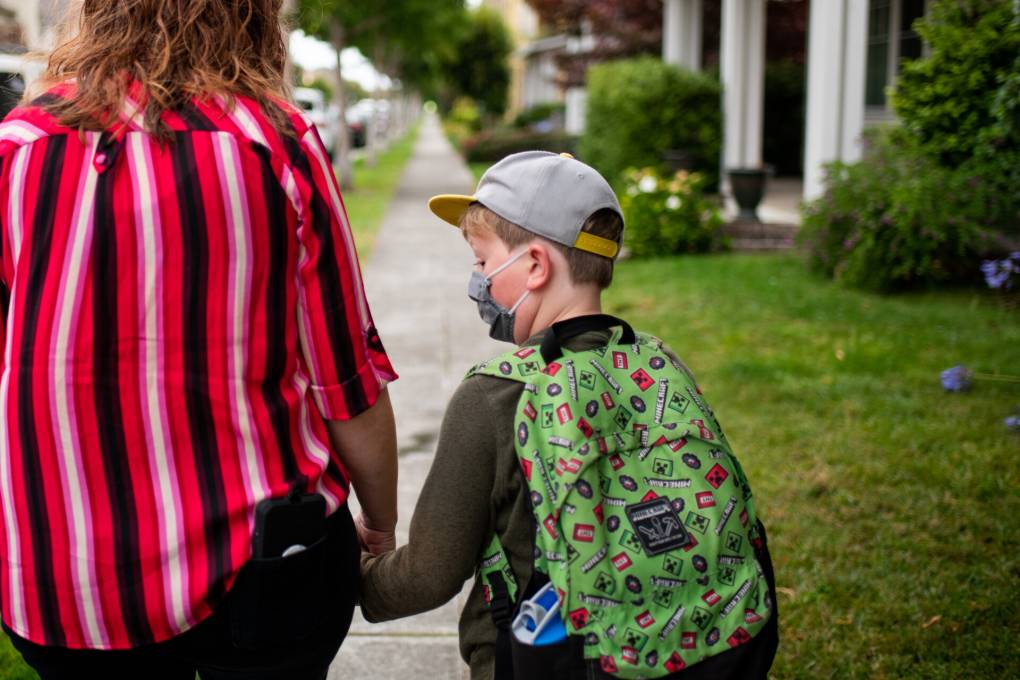 A parent and a child walk on a sidewalk, facing away from the camera. The parent is wearing a red blouse with black and white stripes and the child is wearing a baseball cap and carries a green backpack.