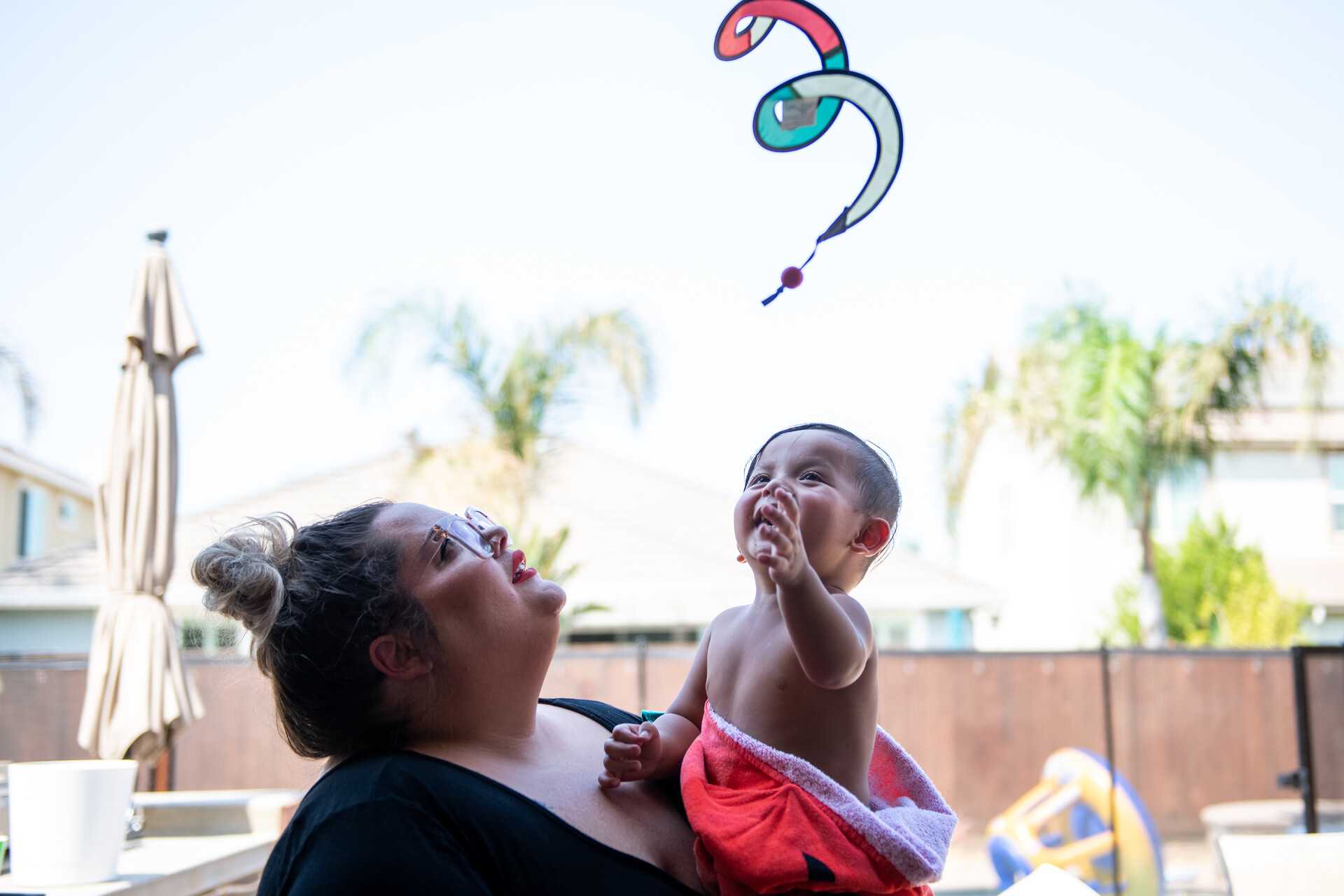 A parent carries their small child in their arms. Both have their bathing suits on and the child wears inflatable lifesavers as both are in the pool. Both are looking up at the sky. Behind them is a backyard and palm trees.