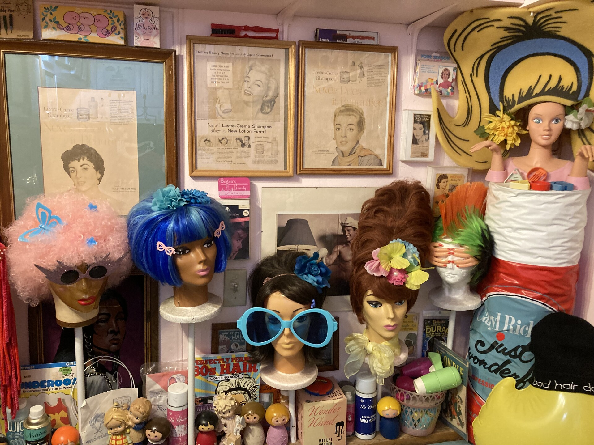 Multi-colored wigs adorn mannequin heads with vintage posters in the background.
