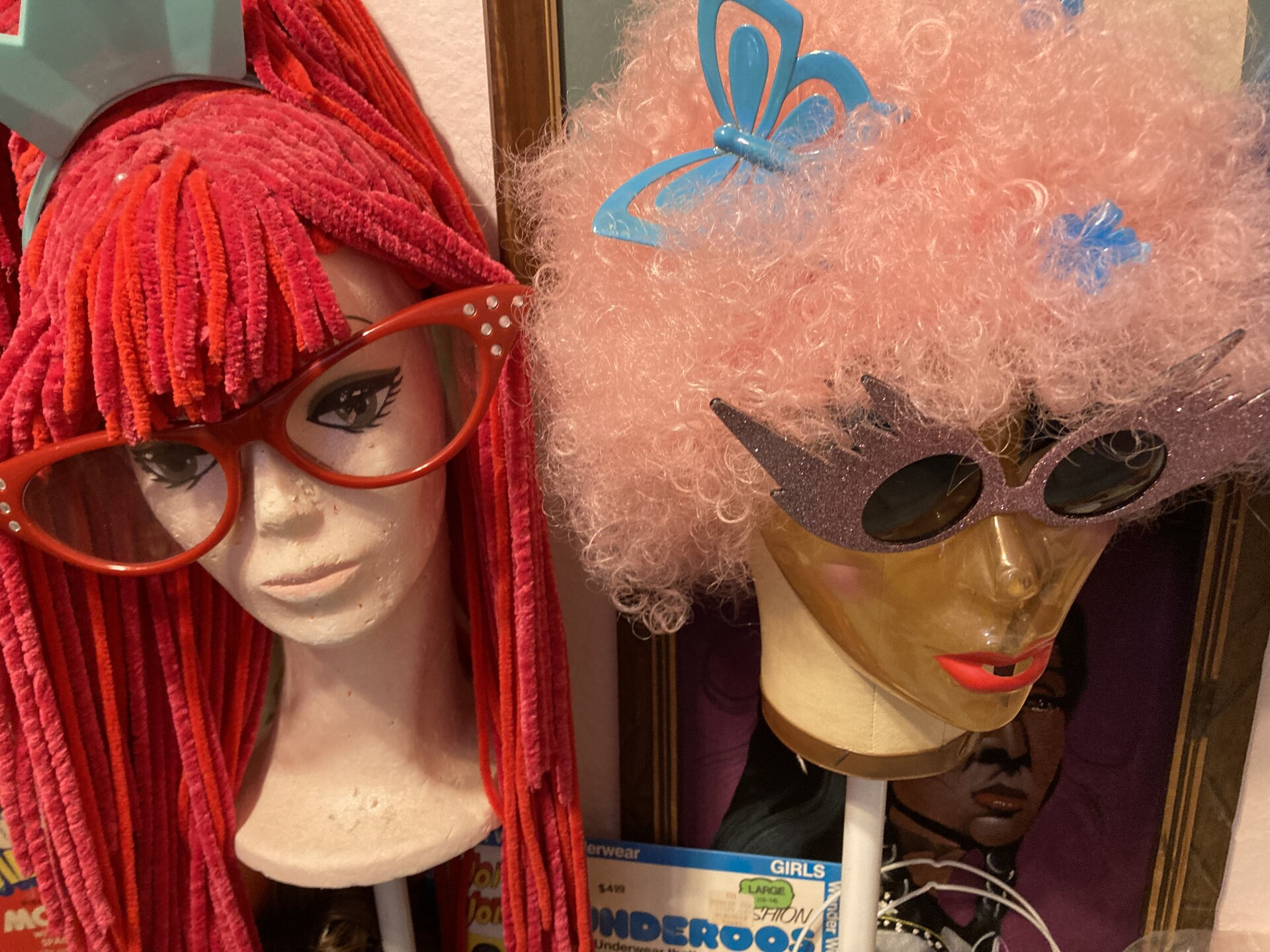 Two mannequin heads sit with a red raggedy-anne wig and a pink curly-haired wig.