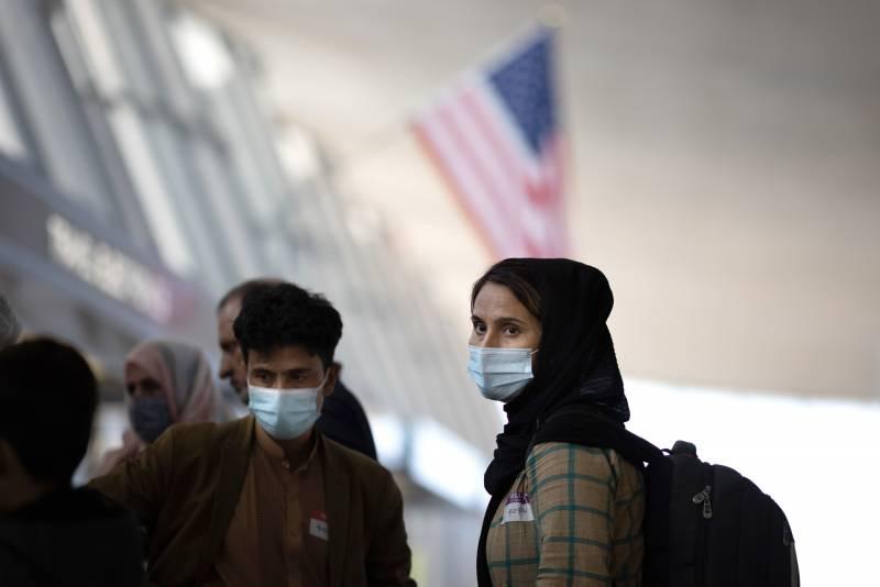 refugees wear masks, head scarves and backpacks inside US airport