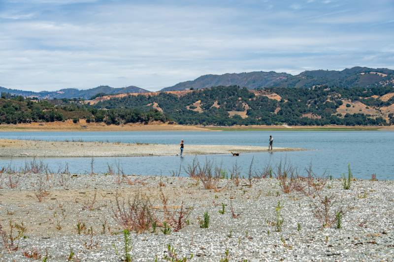 A couple walks their dog near the coast of Lake Mendocino on June 11, 2021.