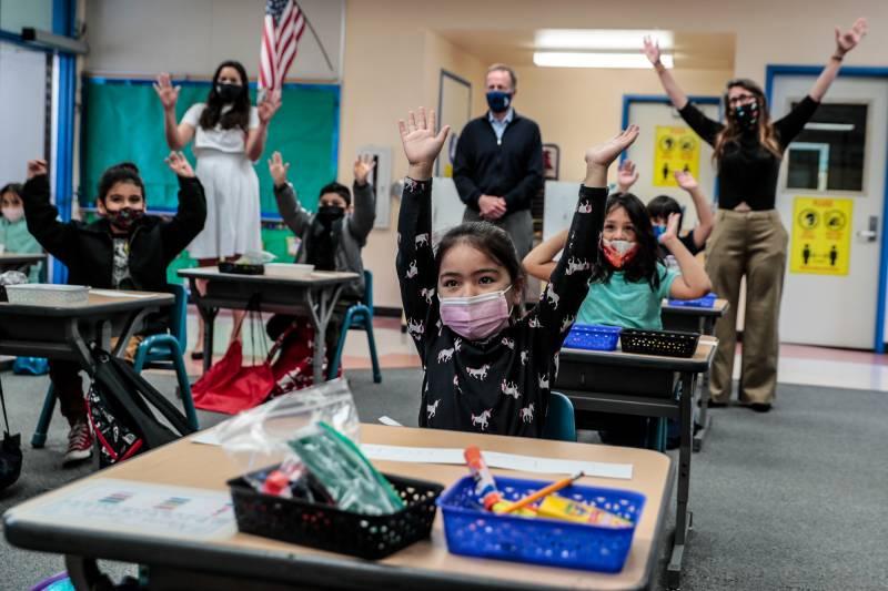 masked kindergartners in masks at desks raising hands