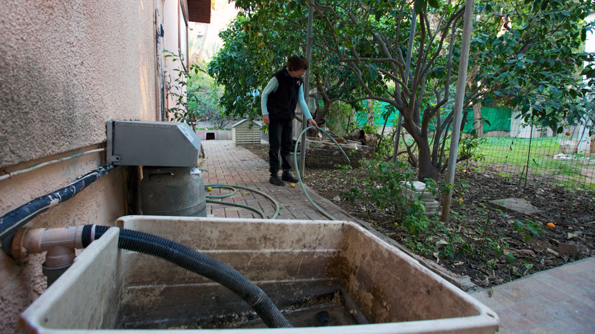 A woman holds a hose connected through a utility sink on the back of her house to water her lawn