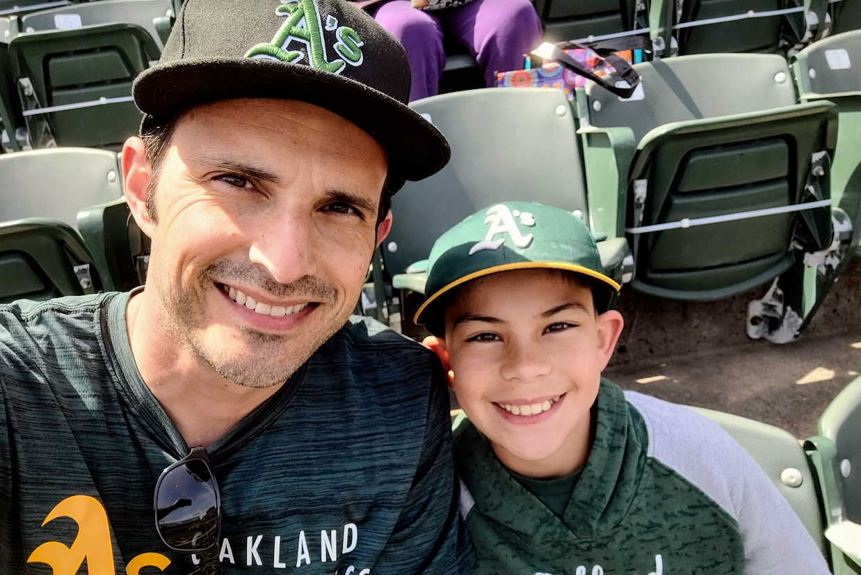 A parent and a child take a selfie. Both are smiling and wear Oakland A's gear.