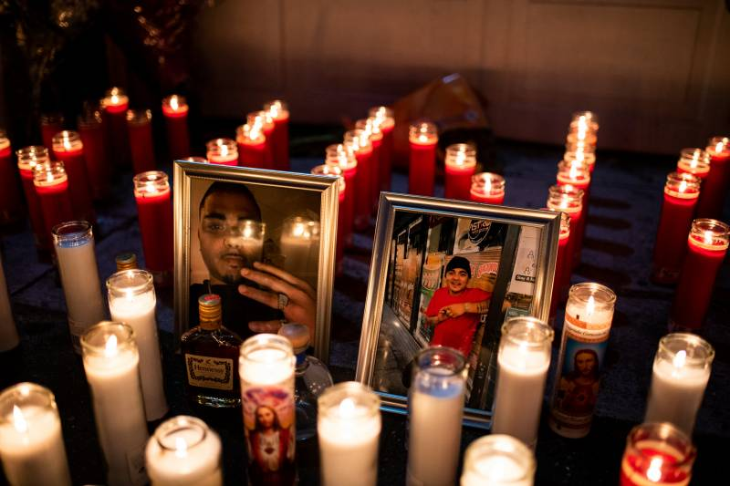 Lit candles surround two photographs.