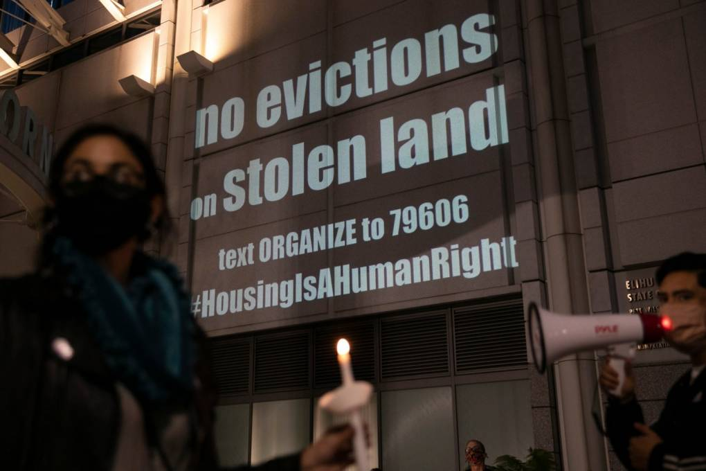 """Protesters hold candles in front of a projection that says, """"no evictions on stolen land."""""""