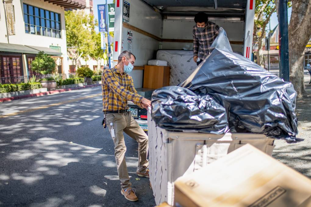 Two men, one inside the back of a truck and one on the street, unload large black garbage bags into a large rolling laundry cart.